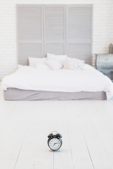 Alarm clock on floor near bed with white linen
