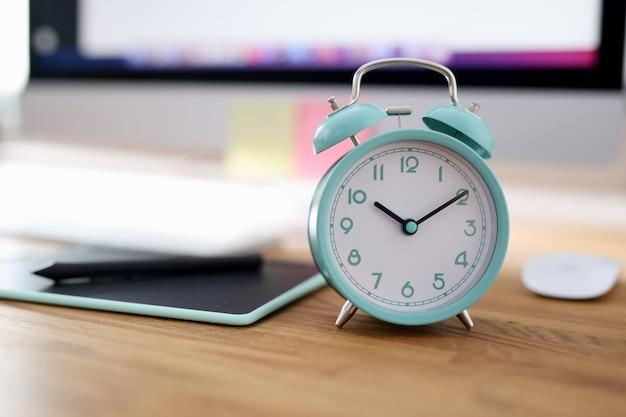 Будильник на десять утра стоит на рабочем столе в офисе. концепция рабочего дня менеджера