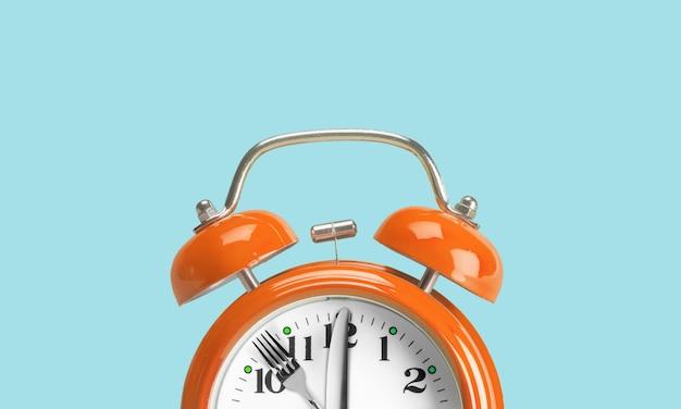 알람 시계. 시계 바늘 대신 포크와 나이프. 간헐적 단식의 개념, 점심시간,