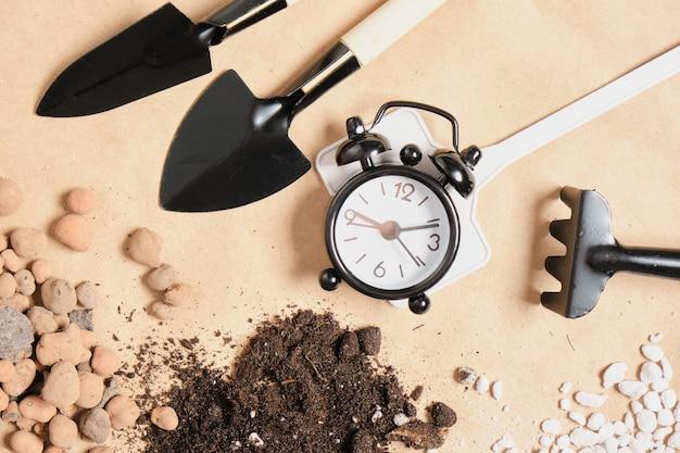 目覚まし時計、ガーデニングアイテム、クラフト紙の土壌添加物と肥料、コピー場所、ガーデニングのコンセプト、種子を植える時間