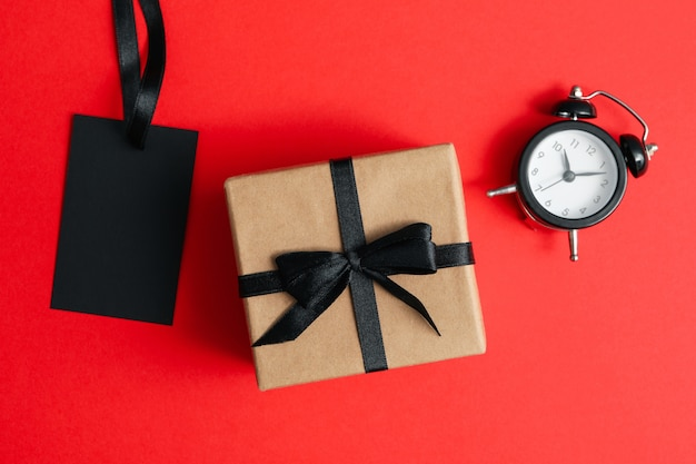 Alarm clock, gift box and tag on red