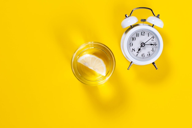 Alarm clock and a glass of water with lemon