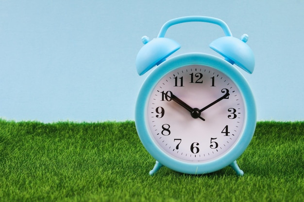 Alarm clock on grass or lawn background. blue alarm clock with fresh green grass.