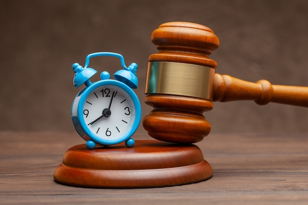 Alarm clock and hammer judge gavel on brown background