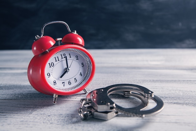 Alarm clock and handcuffs on the table
