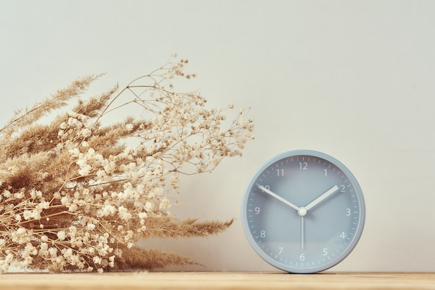 Alarm clock and homemade vase with dries plant on wooden table