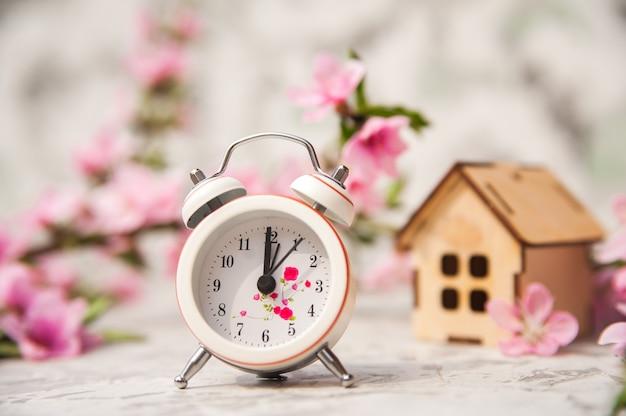 Будильник, дом, цветущая ветка весной.