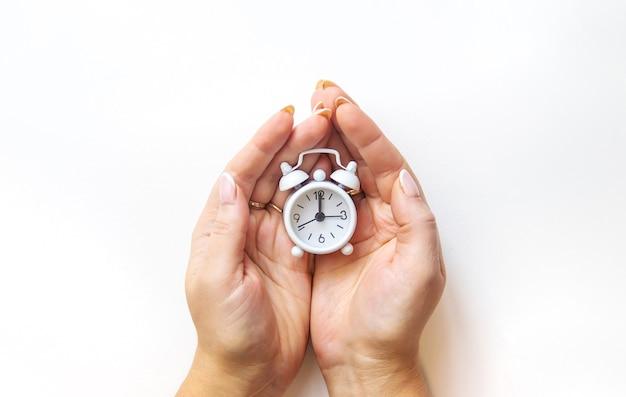 흰색 바탕에 손에 알람 시계입니다. 선택적 초점입니다.
