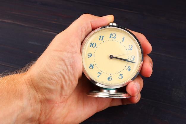 暗い表面に人間の手で目覚まし時計