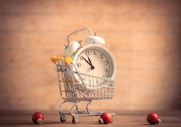 木製のテーブルの小さなショッピングカートの目覚まし時計