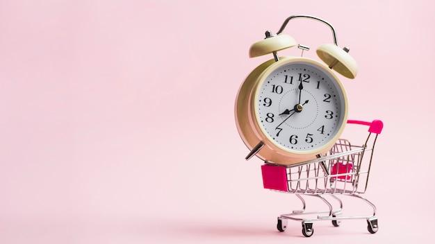 Будильник в миниатюрной тележке для покупок на розовом фоне