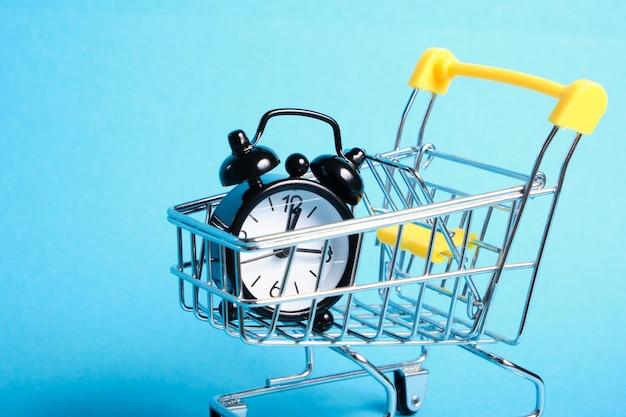 파란색 배경 복사 공간에 미니어처 쇼핑 트롤리에 알람 시계