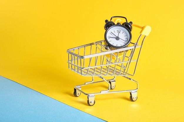 노란색 배경 복사 공간에 미니어처 쇼핑 트롤리에 알람 시계