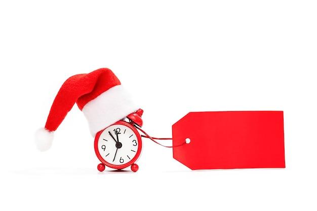 Будильник в шапке санта-клауса с пустым знаком для надписи красным