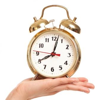 女性の手で目覚まし時計