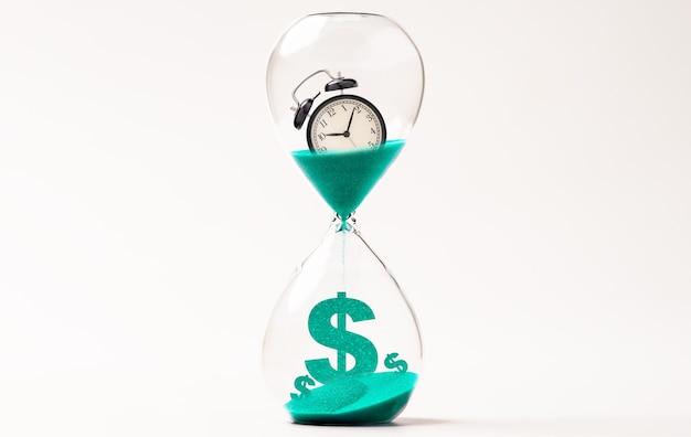 모래시계 안에 있는 알람 시계와 미국 달러 기호, 돈, 시간 관리 개념에 대한 카운트다운.