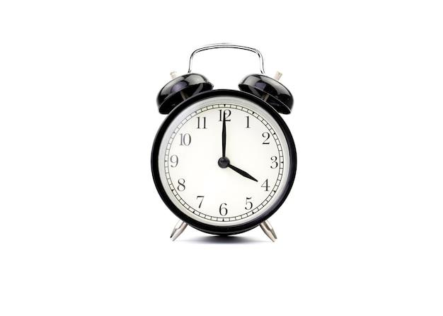 白で隔離された目覚まし時計は4時を示しています