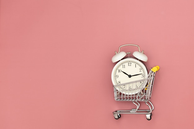 Alarm clock in a metal shopping cart on pink background