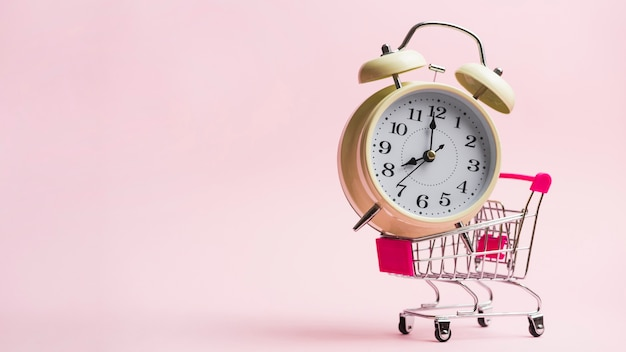 Alarm clock in miniature shopping trolley against pink background