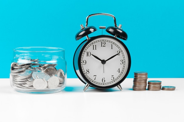 Alarm clock and money coins on the table.