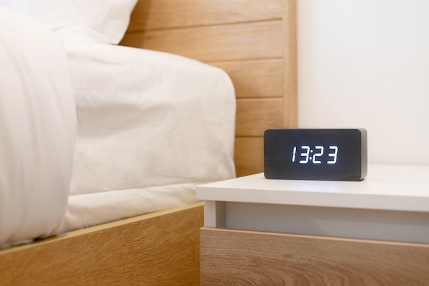 Alarm clock near the bed in the bedroom