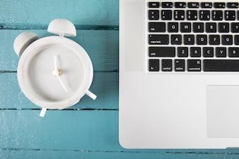 Alarm clock near laptop