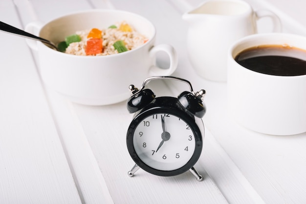 Alarm clock and oatmeal breakfast on white table