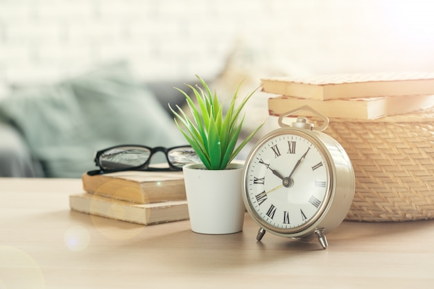 Alarm clock and office stationery objects close up on wooden table