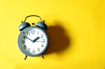 Alarm clock on a bright  yellow background