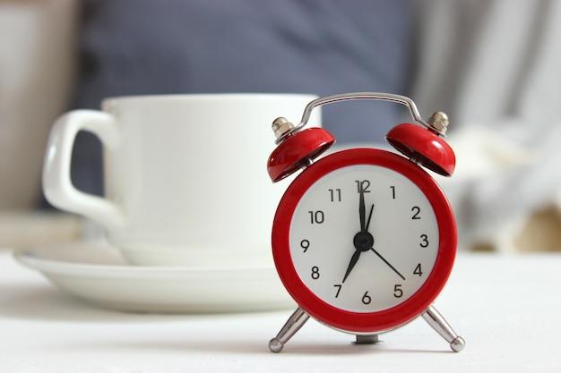 Будильник на цветном фоне с чашкой кофе и канцелярскими принадлежностями