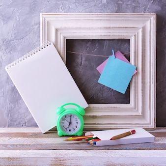 Будильник на рамке пустой блокнот и карандаши на деревянном столе