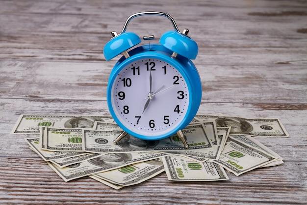 紙幣の山の上の目覚まし時計
