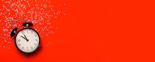 축제 반짝이와 빨간색 배너 배경에 알람 시계. 새 해 이브 최소한의 배경 개념입니다.
