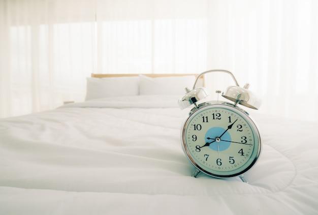 太陽の光で朝の寝室のベッドの上の目覚まし時計。