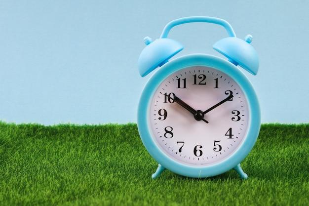草や芝生の背景に目覚まし時計。新鮮な緑の草と青い目覚まし時計。