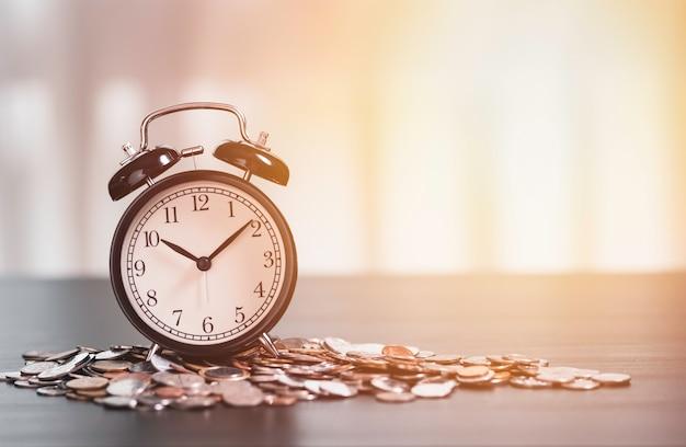 ビジネス投資時間概念のコインの山の目覚まし時計。