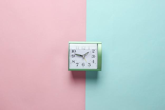 パステルカラーの紙に目覚まし時計。トップビュー、ミニマリズム