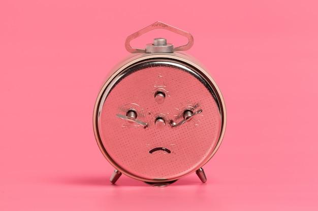 Будильник на розовом фоне