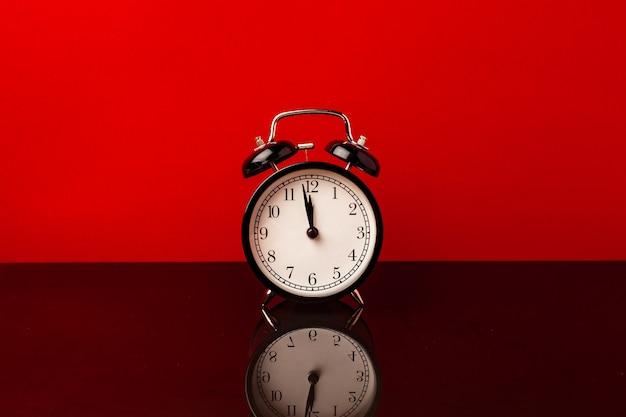 赤い背景の正面図の目覚まし時計