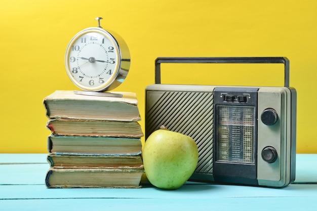 Будильник на стоге старых книг, радиоприемник, яблоко на желтом цвете.