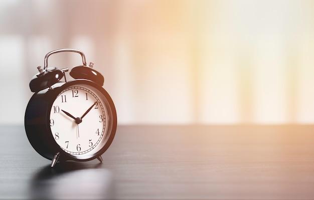 ビジネス投資時間概念のテーブルの上の目覚まし時計。