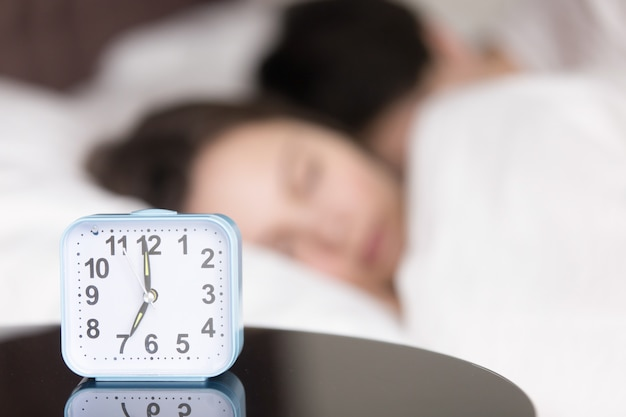 眠っている若いカップルの前のテーブルの上の目覚まし時計