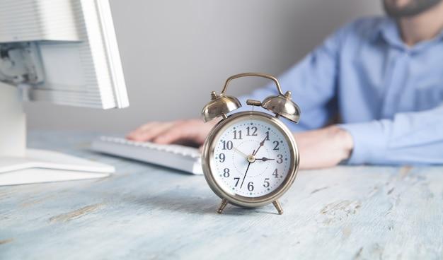 机の上の目覚まし時計。オフィスで働くビジネスマン