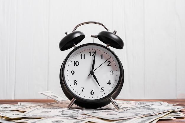 私たちの目覚まし時計白い壁に対して木製の机の上のドル紙幣