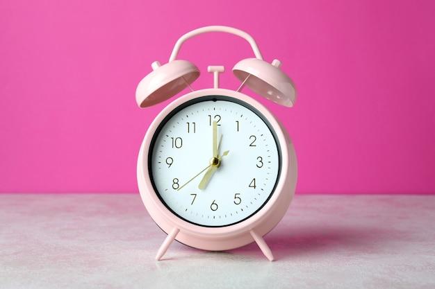 분홍색 배경에 흰색 질감 된 테이블에 알람 시계