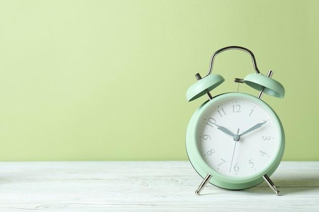그린에 대 한 흰색 나무 테이블에 알람 시계