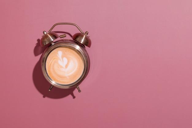 Будильник с пенистым кофе и узором. жесткие тени. утренний подъем с кофе на завтрак концепции с копией пространства