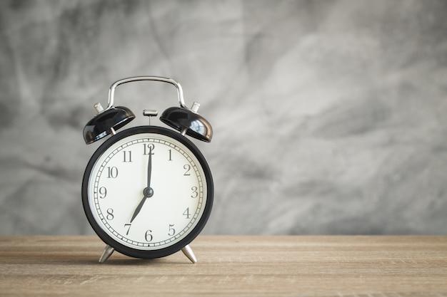 木製テーブルとコピースペースに目覚まし時計
