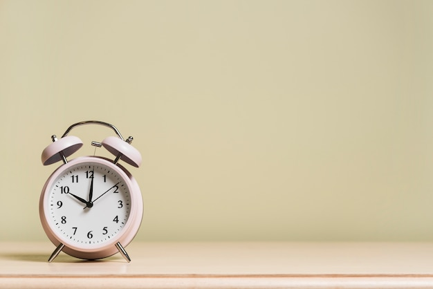 Будильник на деревянном столе показывает время 10 часов против цветной стены