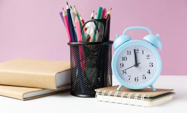 학교 개념을 다시 교실에서 배경에 나무 테이블에 알람 시계
